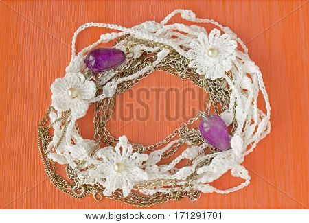 Handmade crocheted cotton organic lace wreath. White crochet frame pattern handicraft background needlework creative craft. Bright crochet wreath with flowers amethyst jewelry place for text poster