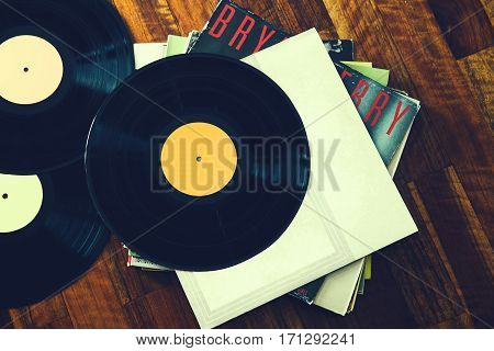 Old vinyl record and a collection of albums on wooden background. Toned image