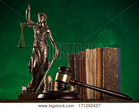 brown gavel with a brass band and statue of justice on wooden table.