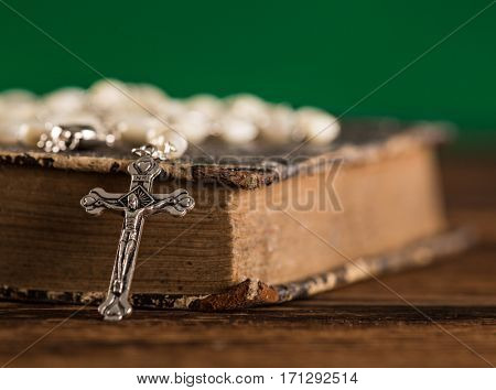 Closeup of iron Christian cross necklace next to holy Bible