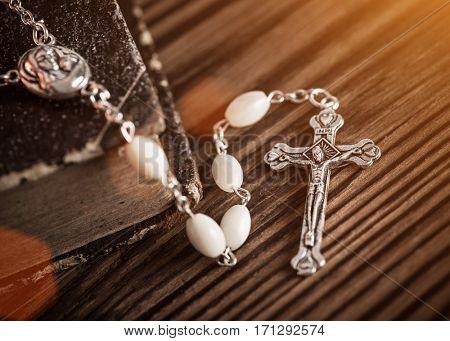 Closeup of iron Christian cross necklace next to holy Bible