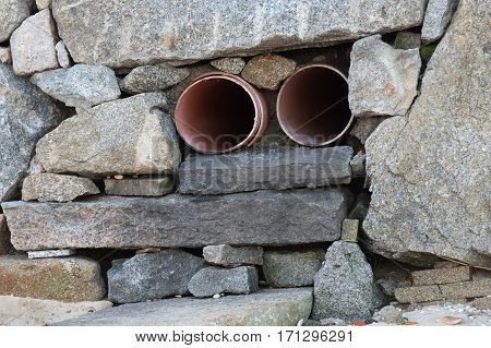 image of sewage pipe in the stone wall