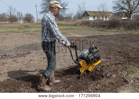 Man working in the garden with garden tiller. Garden tiller to work. Man with tractor cultivating field at spring. Farmer loosens soil by petrol cultivator