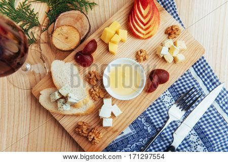 Cheese plate with blue cheese Dor, parmesan cheese, Brie, Camembert and Roquefort and walnuts on the table to maintain a tree close up