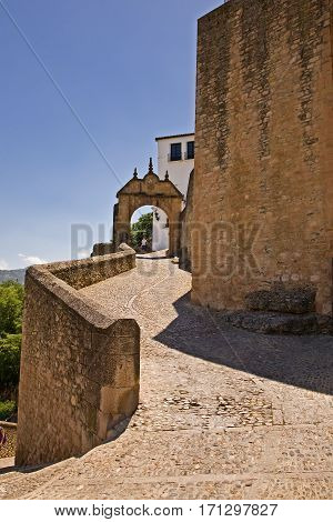 Steep back entrance to the walled town of Ronda, Spain. With gate.