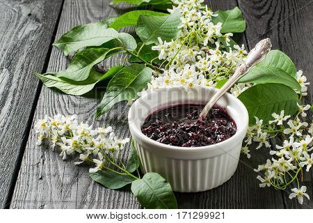 Medicinal plant bird cherry (Prunus padus). Flowering branches and jam on a dark old wooden table. Selective focus