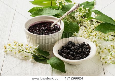 Medicinal plant bird cherry (Prunus padus). Flowering branches dried berries and jam on a white wooden background. Selective focus