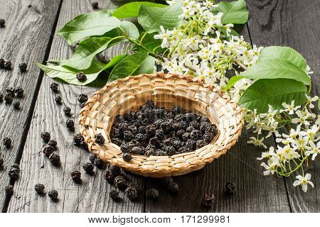 Medicinal plant bird cherry (Prunus padus). Flowering branches and dried berries in a wicker bowl on a dark old wooden table. Selective focus