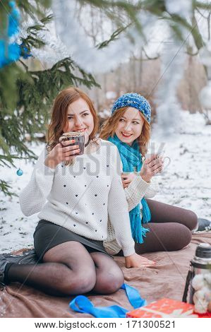The girls sit near trees in winter on snow and drinking tea from circle
