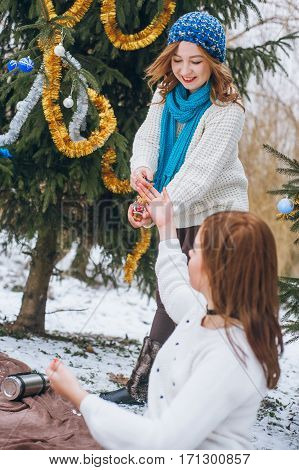 Girls decorate a Christmas tree with colorful decorations