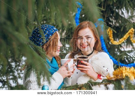 Girls at the trees in winter drink tea with circle