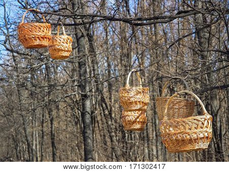 Trade of Handicrafts in the street in the spring. Wicker baskets hung on the branches of trees