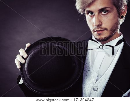Elegantly Dressed Man Holding Black Fedora Hat