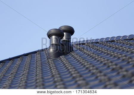 Ventilation chimneys on the roof of a new home.