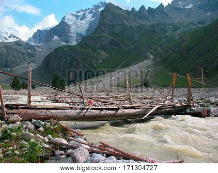 Old wooden bridge over the flashy river in the Caucasus Mountains of Russia.