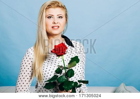 Romance valentine day gifts concept. Beautiful blonde woman holding red rose looking melancholic