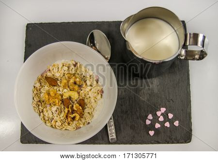 top view on nutritious breakfast of oatmeal with fruit and milk on a black stone plate and purple hearts morning meal
