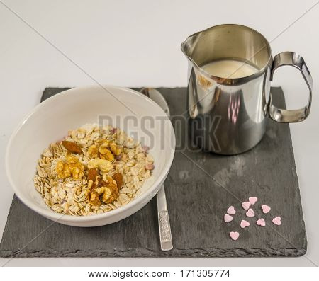 nutritious breakfast of oatmeal with fruit and various nuts with a jug of milk on a black stone plate and purple hearts