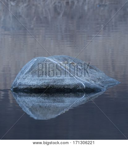 Large boulder in a river with its reflection in the calm water and reflection of reeds in the background