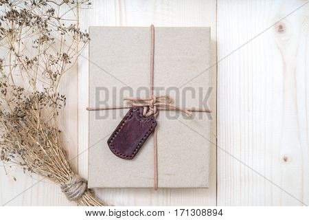 Gift boxes with labels made of leather with rope on gunny sack vintage style background