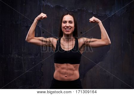 Close-up of fitness model showing trained biceps. Slim model showing the great relief of trained muscled arms and body. Biceps concept. Fitness sport training lifestyle