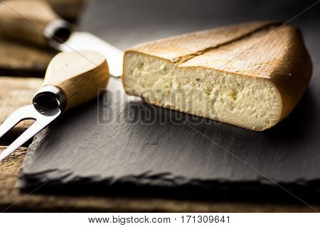 Chunk of smoked goat cheese with fork and knife in the background black stone board vintage wood boxrustic interior close up