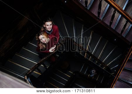 couple of young people on the wooden stairs in the entrance of an old house