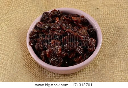 Condiment dish of dried cherries lightly covered in sunflower oil to preserve softness