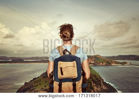 Happy traveler with a backpack enjoying the view of a tropical coast on a background the mountains. Young backpacker traveling along Asia happy female walking discovering world summer vacation concept