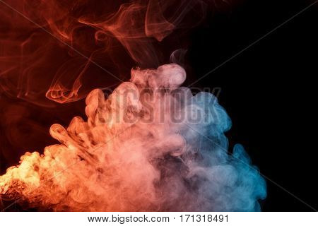 Abstract smoke Weipa. Personal vaporizers fragrant steam. The concept of alternative non-nicotine smoking. Orange turquise smoke on a black background. E-cigarette. Evaporator. Taking Close-up. Vaping.