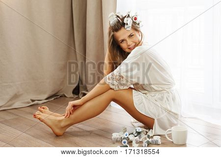 Young attractive housewife sitting on the floor near the window. Girl in a bathrobe and curlers drinking morning coffee. Good morning. She makes hairstyle