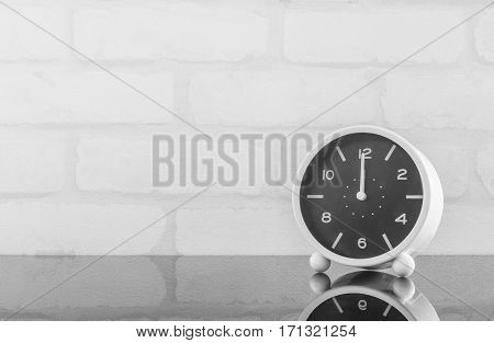 Closeup black and white alarm clock for decorate in 12 o'clock on black glass table and white brick wall textured background in black and white tone with copy space