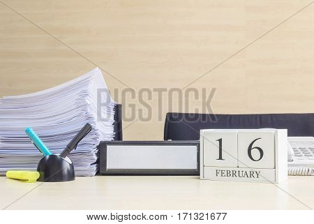 Closeup white wooden calendar with black 16 february word on blurred brown wood desk and wood wall textured background in office room view with copy space in selective focus at the calendar