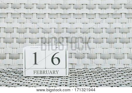 Closeup surface white wooden calendar with black 16 february word on blurred weave wood chair textured background with copy space in selective focus at the calendar