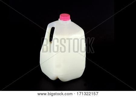 gallon of milk bottle with pink cap isolated on black background