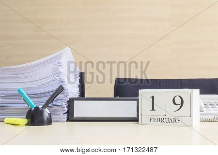 Closeup white wooden calendar with black 19 february word on blurred brown wood desk and wood wall textured background in office room view with copy space in selective focus at the calendar