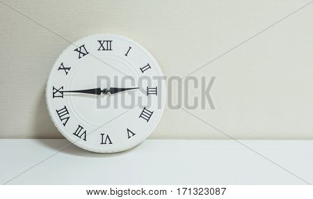 Closeup white clock for decorate show a quarter to three p.m. or 2:45 p.m. on white wood desk and cream wallpaper textured background with copy space