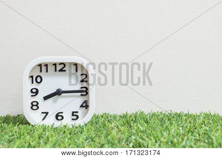 Closeup white clock for decorate show a quarter past eight or 8:15 a.m. on green artificial grass floor and cream wallpaper textured background with copy space