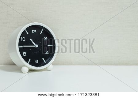 Closeup black and white alarm clock for decorate in a quarter to eleven or 10:45 a.m. on white wood desk and cream wallpaper textured background with copy space