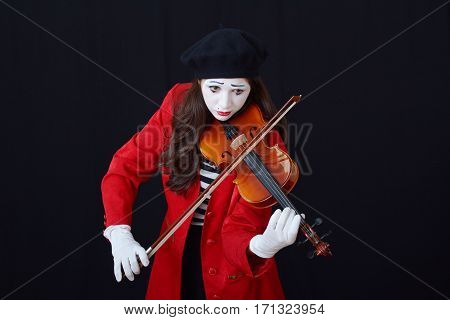 young brunette woman in a suit holding an old mime violin on a dark background