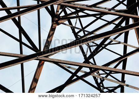 Rusty detail of power lines pylon over blue sky background
