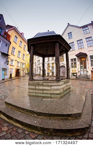 An old well in the middle of the old town of Tallinn Estonia. The well is on a square surrounded by pittoresque old buildings.