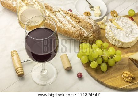 A photo of a wine and cheese tasting, with bread, grapes, glasses of red and white wine, a corkscrew and a cork