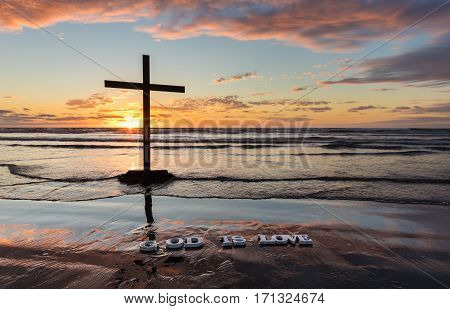 Black Cross on a beach with the words 'God is Love' on the wet sand at sunset.