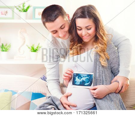 Happy Young Couple Expecting Baby. Beautiful Pregnant Woman and Her Husband Together holding ultrasound picture of their baby, Pregnant Belly. Expectant parents, Mom and Dad waiting for their baby. poster
