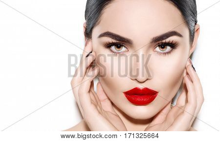 Beautiful Young Brunette Woman face portrait. Beauty Model Girl with bright eyebrows, perfect make-up, red lips, touching her face. Sexy lady makeup for party. Isolated on white background
