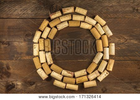 Many wine corks on a dark wooden background texture, forming a frame for copy space. A horizontal design template for a tasting invitation or restaurant menu
