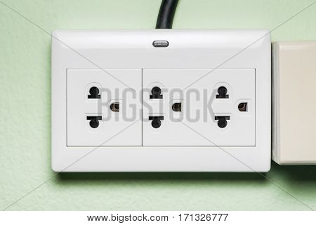 White AC Electric Outlet with Indicator Lamp on Green Wall