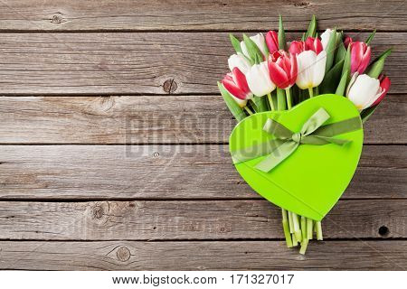 Colorful tulips bouquet and gift box on wooden background. Red and white. Top view with space for your text