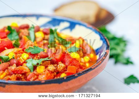 Chili con carne in a clay bowl on a concrete background. Traditional Mexican cuisine